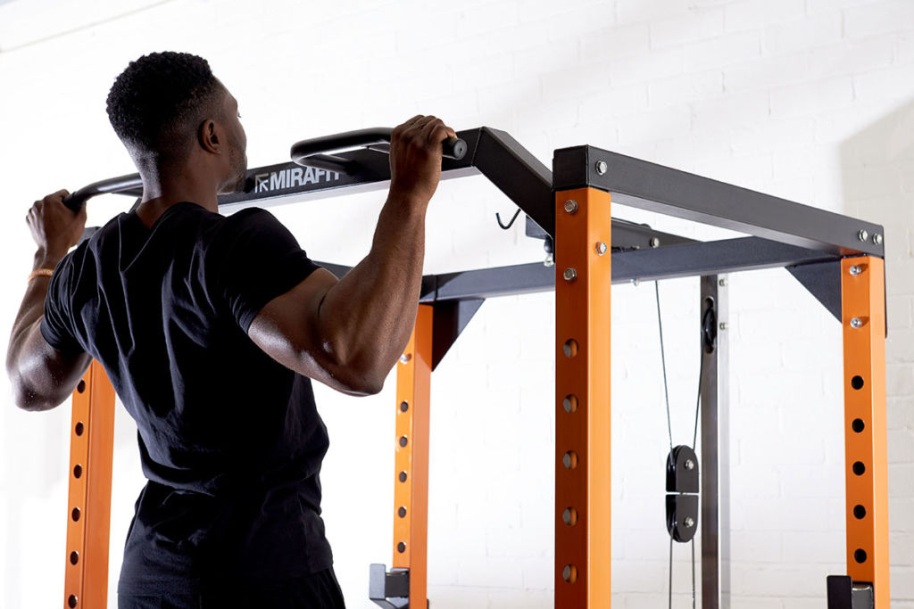 fitness expert does a chin up on a mirafit power rack