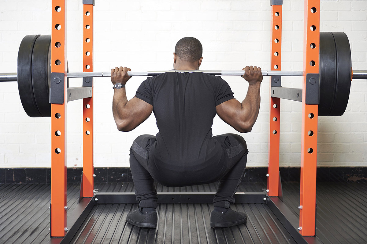 young man doing a squat using a power cage for support