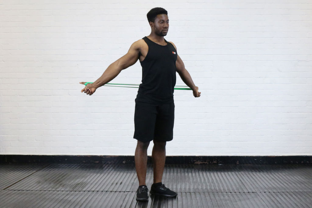 fitness expert uses mirafit resistance band to finish pass through stretch