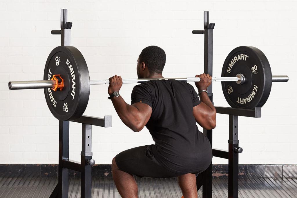 Fitness expert using a Mirafit adjustable squat rack