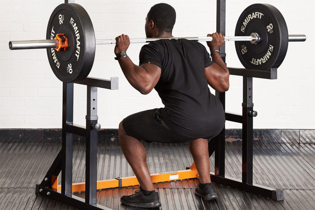 fitness expert using mirafit adjustable squat rack kit to squat