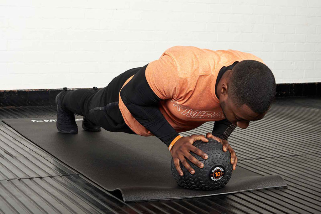 Man doing a push up holding a Mirafit tyre tread slam ball
