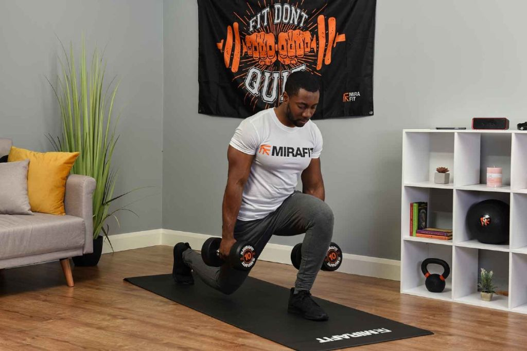 man demonstrating a lunge on an exercise mat holding dumbbells in a living room