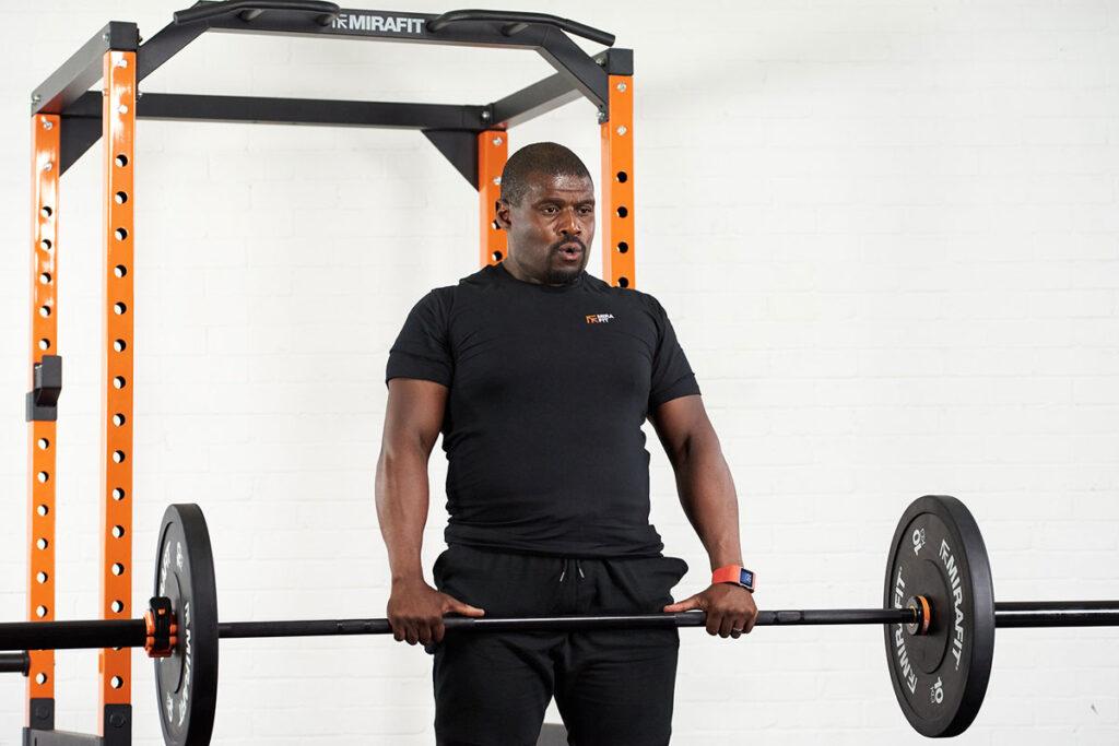 Man deadlifting Mirafit weights in front of a Mirafit Power Rack