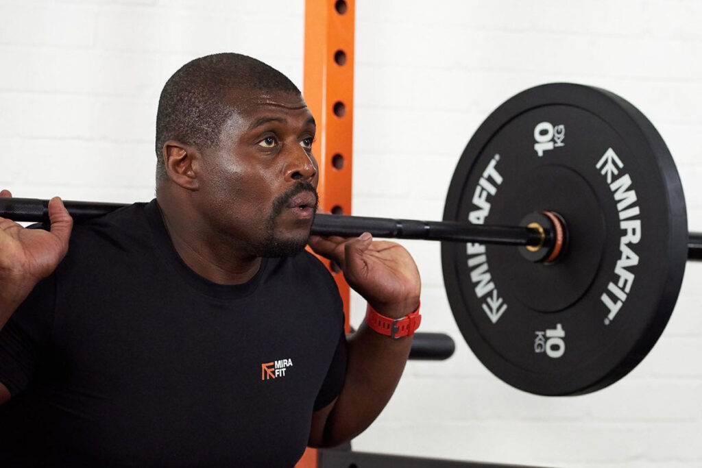Fitness expert and personal trainer Steve Parke squatting with a 10kg Mirafit weight plate