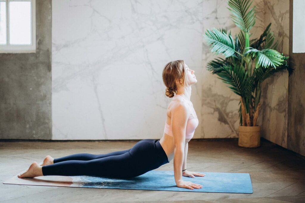 woman performing a yoga pose on a yoga mat