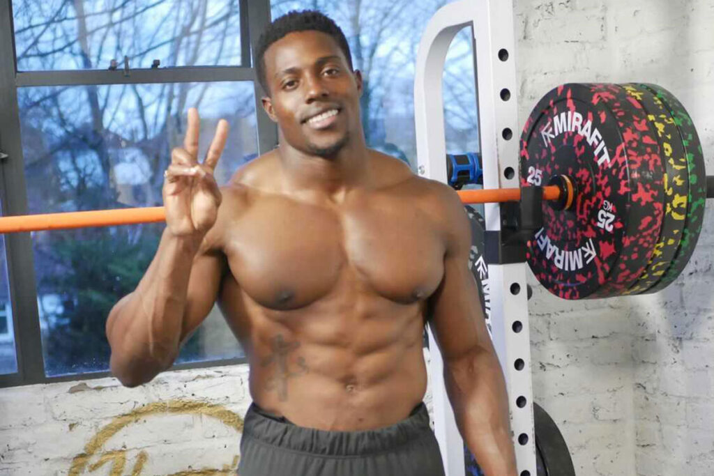 Olympic sprinter Harry Aikines-Aryeetey poses in front of a set of Mirafit weight plates.