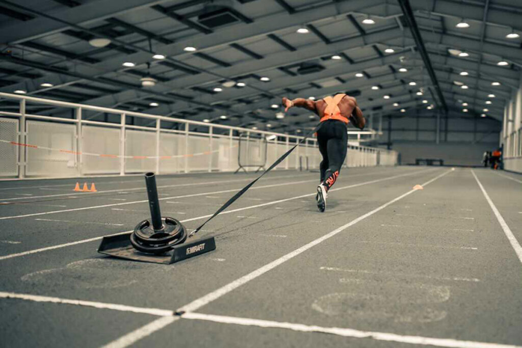 Harry Aikines-Aryeetey sprinting while pulling a Mirafit weight sled