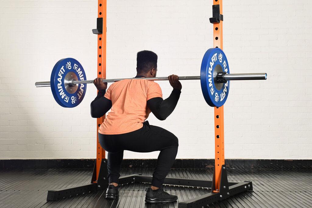 Man squatting in a Mirafit squat rack