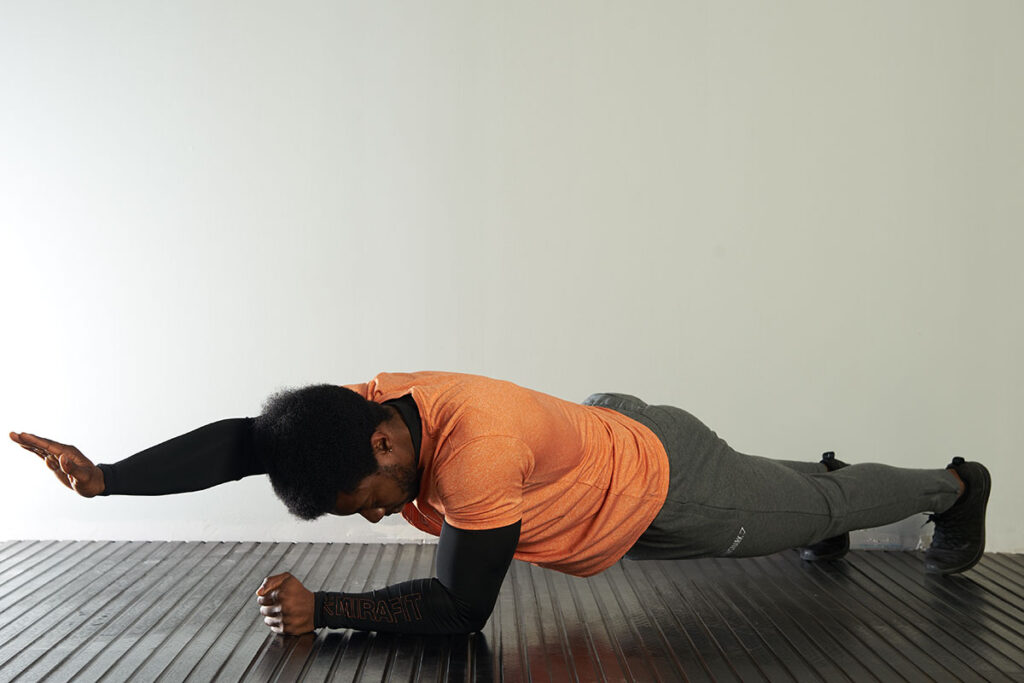 Man performing a single arm plank.