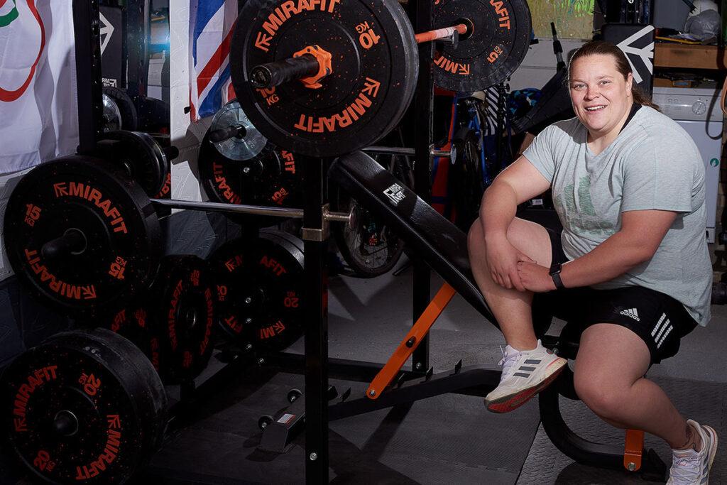 Sophie McKinna sitting on a Mirafit adjustable weight bench