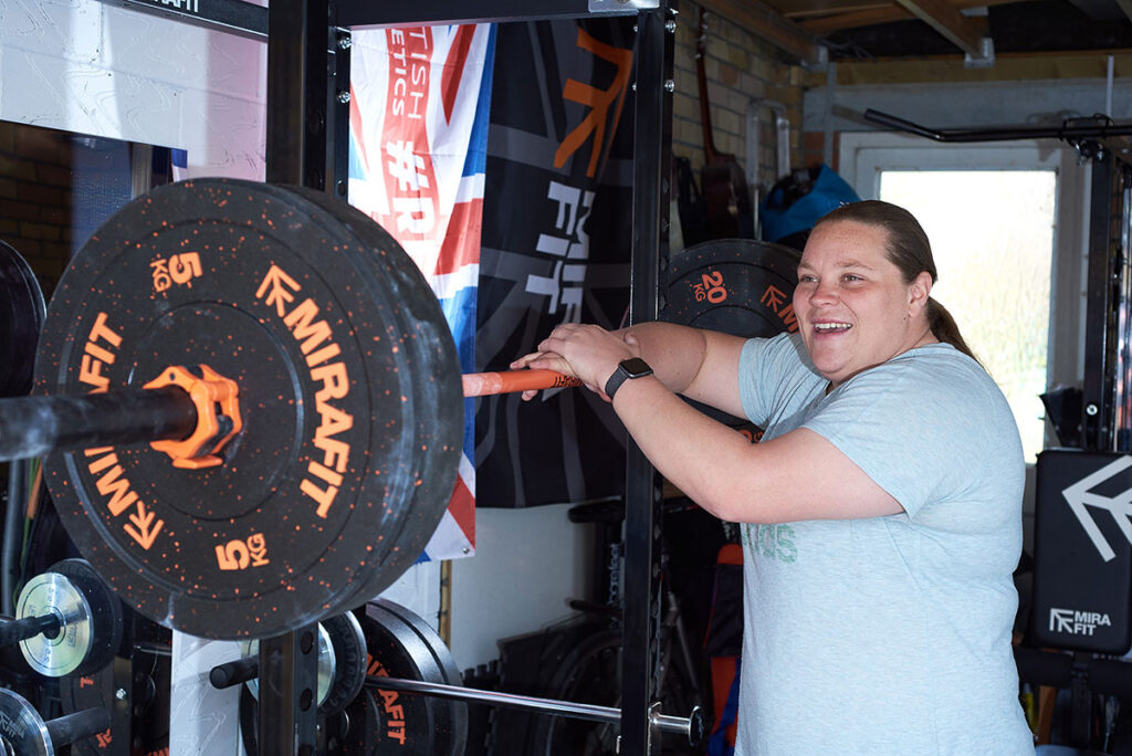Sophie McKinna standing with a Mirafit Barbell and Weight Plates in a garage gym