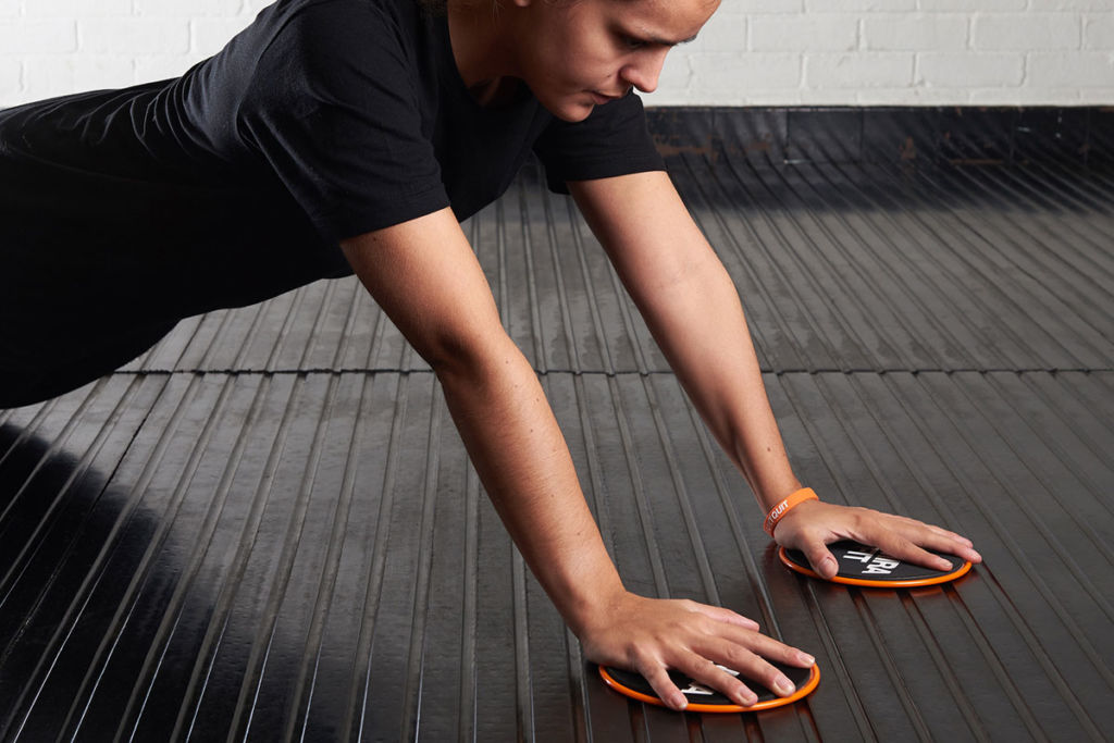 fitness expert uses mirafit core sliders for core and arm exercises
