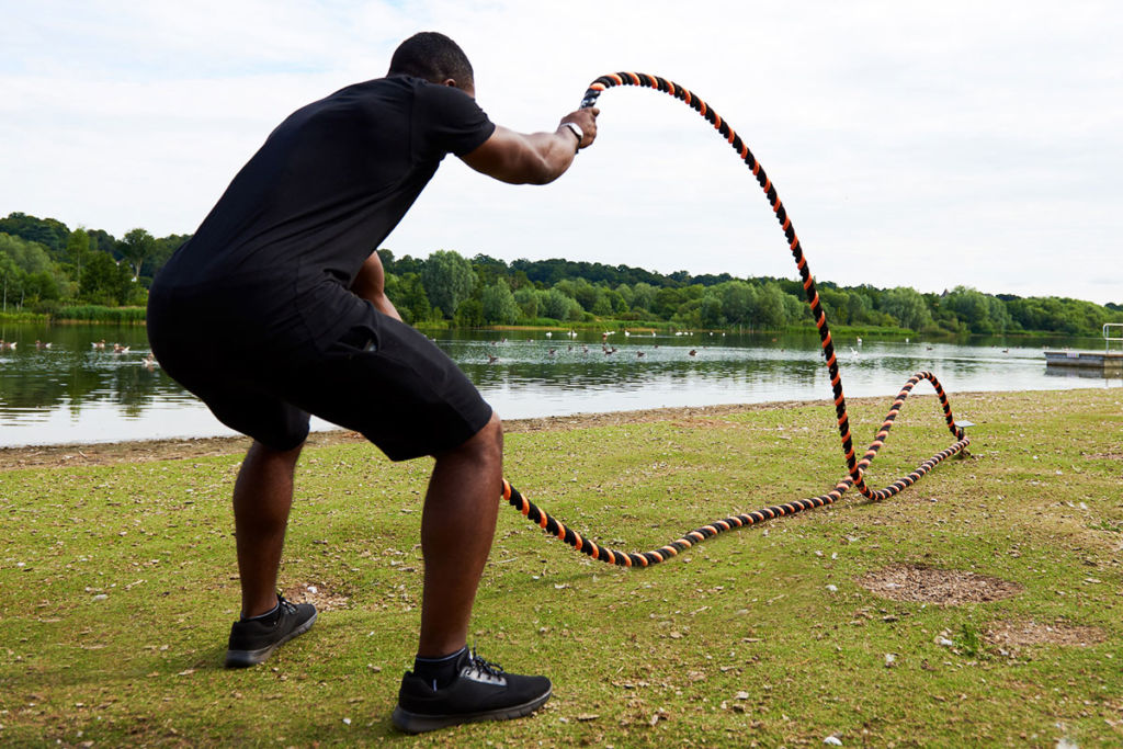 fitness expert performs alternating waves using mirafit battle ropes
