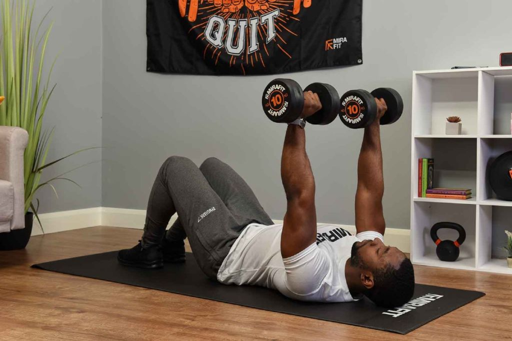 This is an image of a fitness model demonstrating the dumbbell floor press exercise at home.